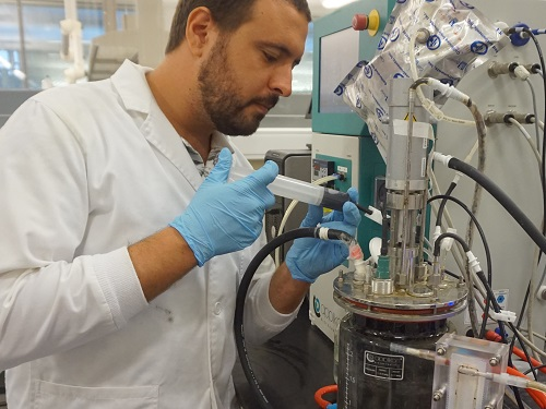 Moustapha Harb collects a water sample from the anaerobic membrane bioreactor.
