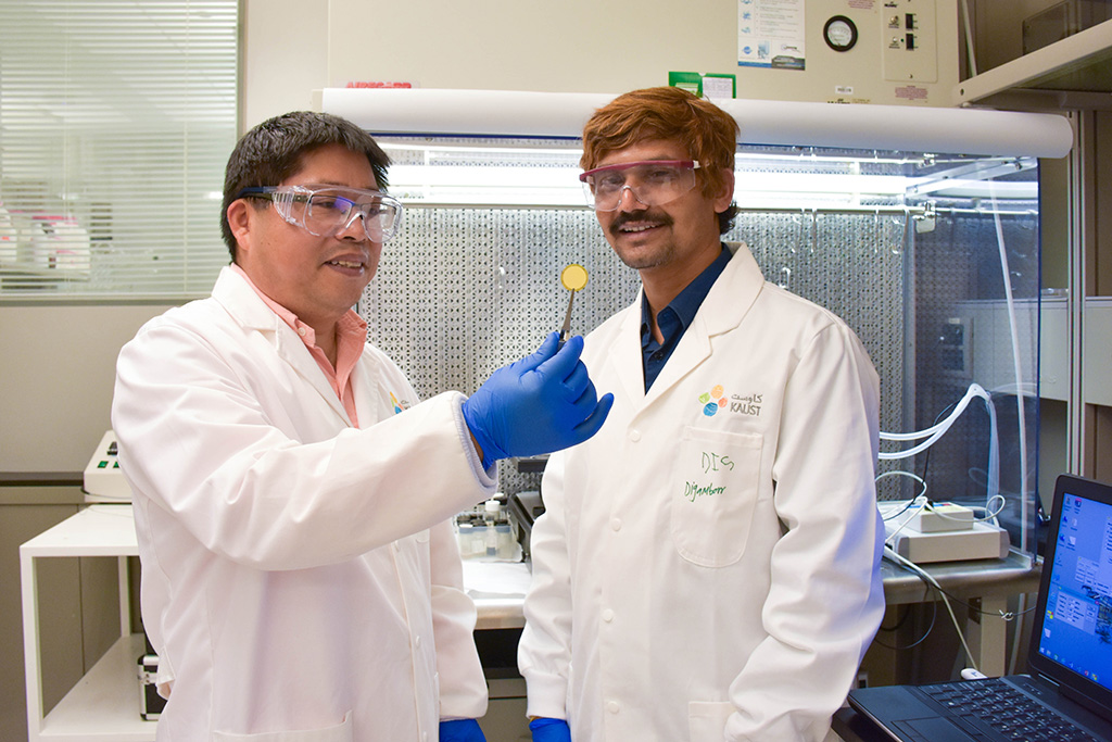 Zhiping Lai (left) holds up the team's high-flux membrane for organic solvent filtration with first author of the paper, Digambar Shinde (right).