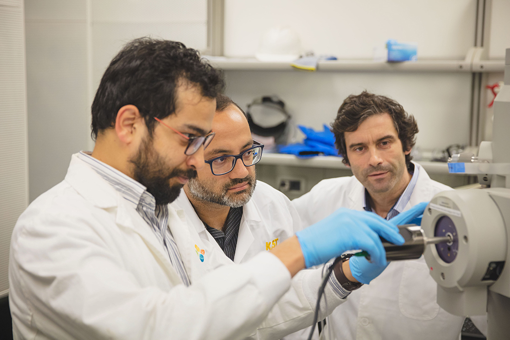 Researchers load a sample of their bent nanowires into the TEM for analysis. (l-r): Nitin Batra, Ahad Syed and Pedro Costa.
