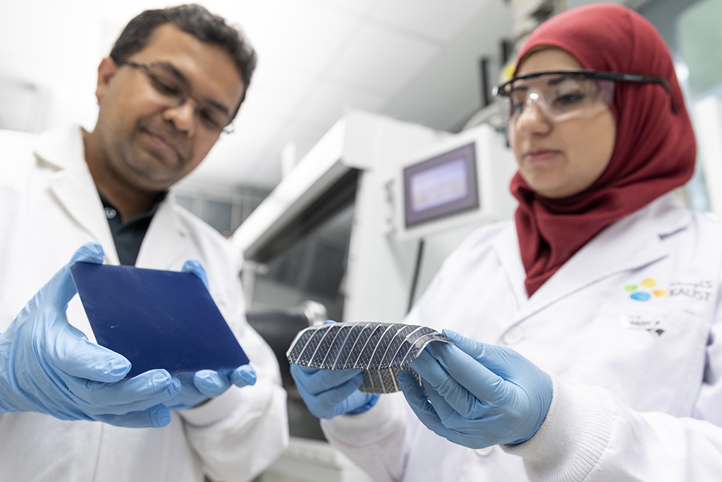 Muhammad Mustafa Hussain (left) and Nazek El-Atab compare the flexibility of their solar cell with the rigid nature of a typical silicon solar cell.