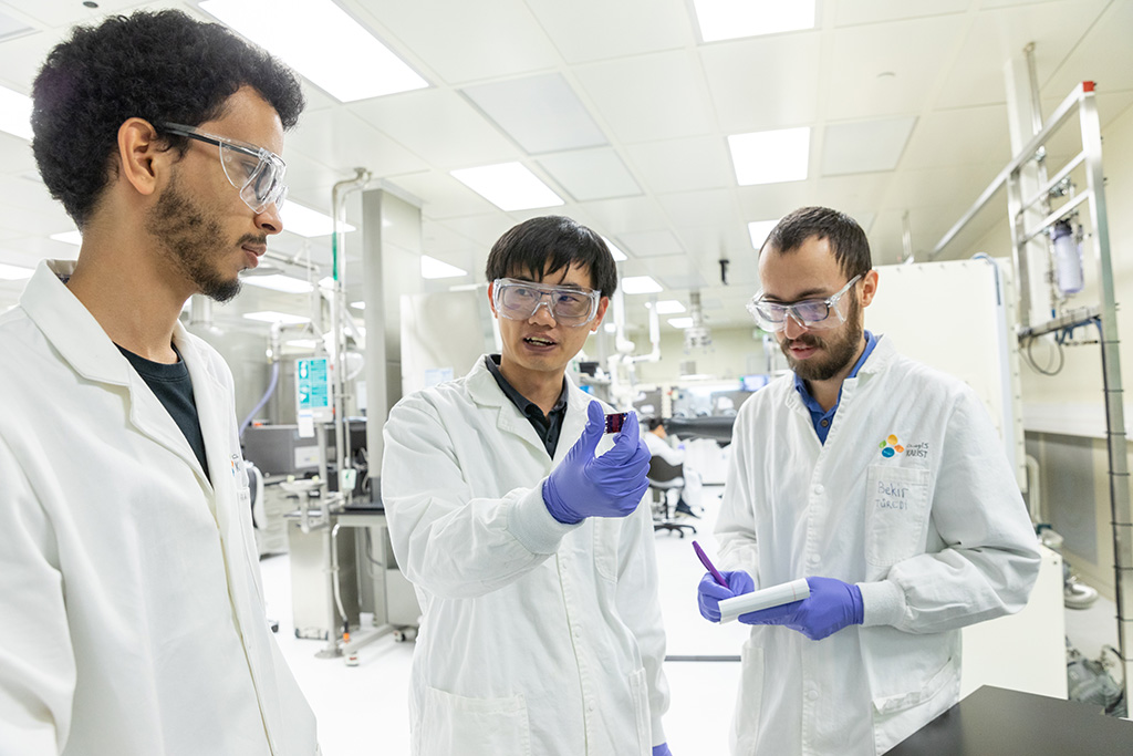 (l-r) Co-authors Abdullah Alsalloum, Xiaopeng Zheng and Bekir Turedi discuss the process for making inverted perovskite solar cells without the use of unstable dopants.